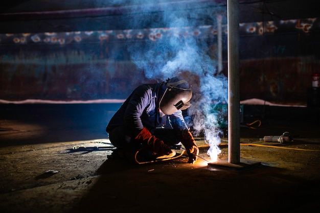 용접 남성 작업자 금속은 제한된 공간 내부의 기계 탱크 플레이트 바닥 건설 석유 및 가스 저장 탱크의 일부입니다.