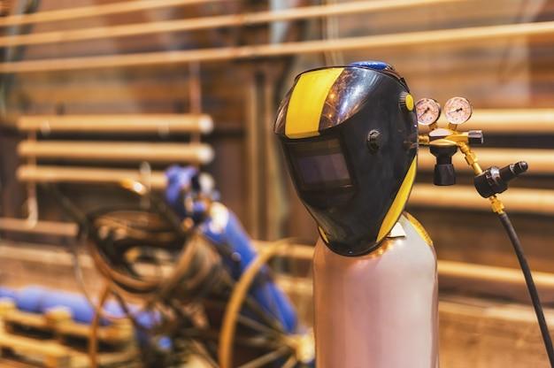 A welding mask hangs on an oxygen tank against a blurry background of welding equipment