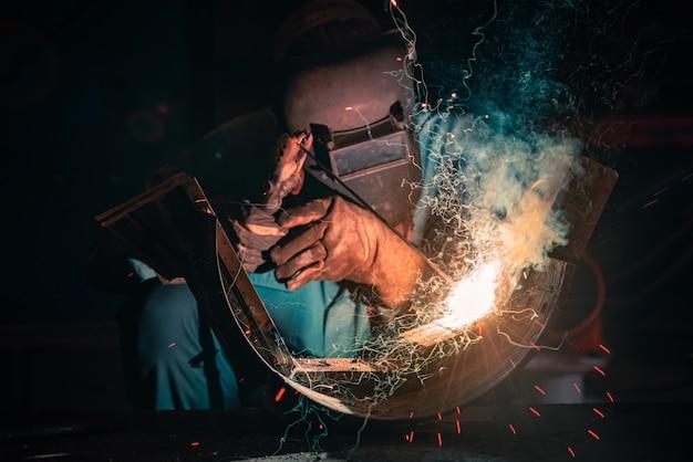 Сварка металлоконструкций и яркие искры в сталелитейной промышленности. синие тона