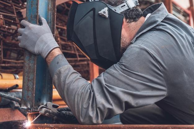 Сварочные работы, человек сварка в мастерской. металлоконструкции и искры. строительство и промышленная концепция.