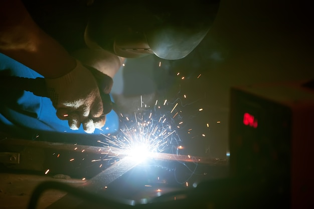 Welding worker in the mask sparks