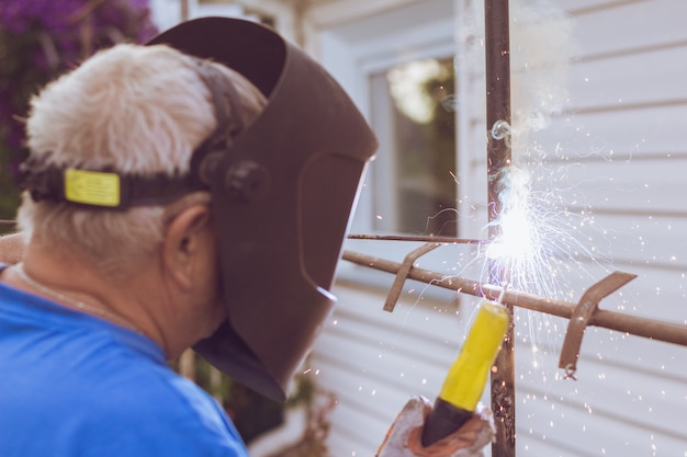Welding worker repairing metal construction
