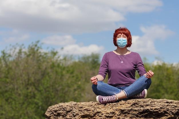 수술용 마스크에 빨간 머리를 한 나이 많은 여성이 연꽃 자세로 푸른 하늘을 배경으로 돌 위에 앉아 있습니다.