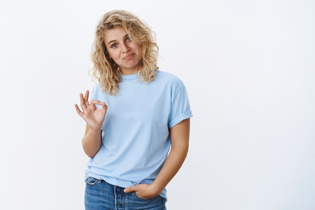 Well, not bad. portrait of woman reacting to boyfriend efforts being impressed showing okay gesture as giving positive feedback about cool trick of friend saying nice work over white wall
