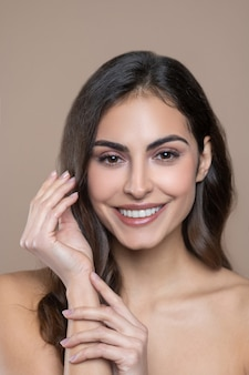 Well-being. beautiful face of young smiling dark-haired woman and her thin graceful hands with manicure