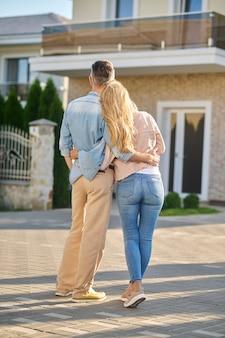 안녕. 화창한 날 야외에서 새 집을 보고 있는 카메라에 등을 대고 서 있는 남녀를 껴안습니다