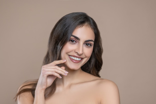 Well-being, mood. smiling long haired young woman with bare shoulders touching hand to beautiful face