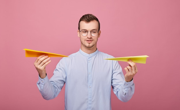A well-bred young man in blue shirt and pc glasses stands with two paper airplanes in his hands