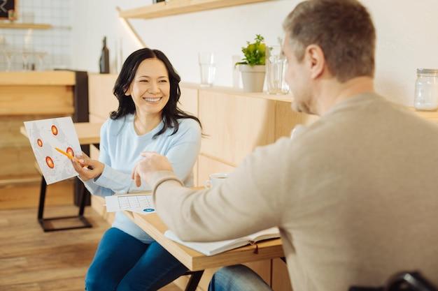 カフェのテーブルに座って笑顔で仕事について話し合っているしっかりした金髪の障害者の男性と美しい陽気な黒髪の女性