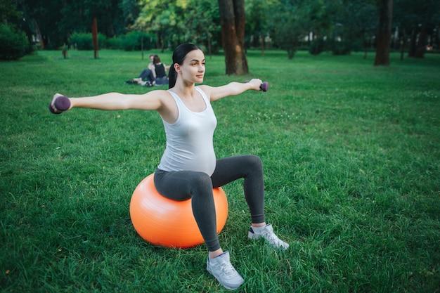 잘 지어진 된 젊은 임신 한 여자 오렌지 피트 니스 공을 공원에서 운동에 앉아. 그녀는 아령을 든다.