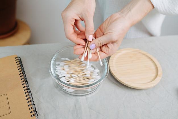 Ухоженные женские руки достают экологически чистые ватные палочки из стеклянной посуды. на столе деревянная крышка.