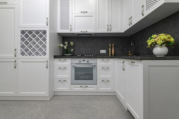Хорошо продуманная деревянная мебель на современной черно-белой кухне в классическом стиле, вид спереди