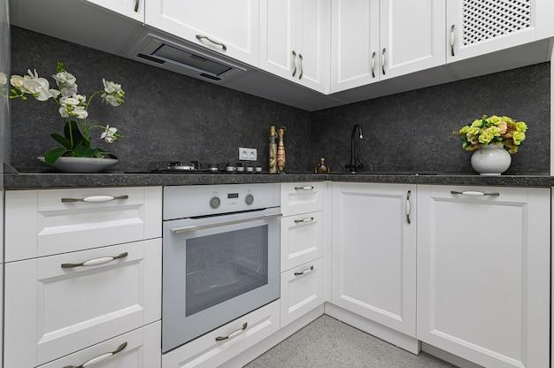 고전적인 스타일의 현대적인 흑백 주방에서 잘 설계된 목재 가구