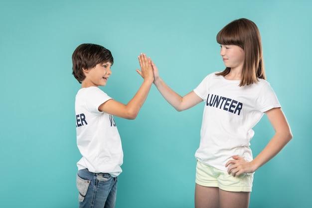 Отличная работа. веселые молодые добровольцы улыбаются и дают пять