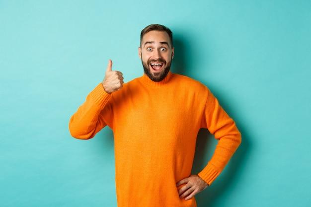 よくやった。親指を立てて、良い仕事を賞賛し、良い製品を推薦し、承認し、満足して笑い、水色の背景の上に立っているハンサムなひげを生やした男。