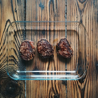 Well done steaks on a wooden background