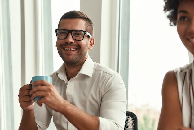 Молодец молодой и красивый мужчина в очках, держа чашку кофе и глядя с улыбкой, сидя с коллегами за офисным столом. деловые люди. мозговой штурм
