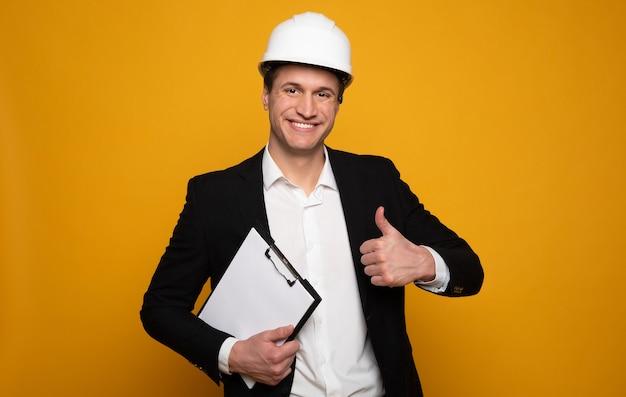 よくやった!フォーマルな服とヘルメットをかぶった若い魅力的な男性がカメラを見て、親指を立てて仕事のメモを持っています。