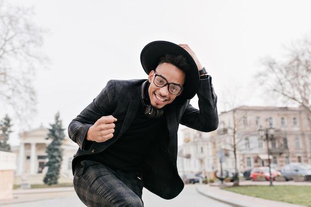 Uomo africano ben vestito che balla nella piazza della città con un sorriso. ragazzo nero che ride che tocca il suo cappello mentre posa all'aperto sotto il cielo grigio.