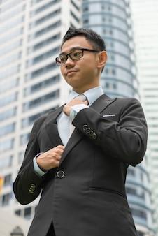 ネクタイを調整する身なりのよいアジアのビジネスマン