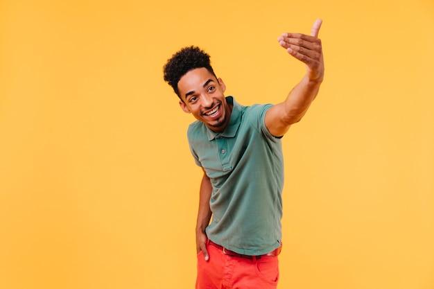 감정적으로 포즈를 취하는 짧은 머리를 가진 단정 한 흑인 남자. 녹색 티셔츠에 즐거운 남자의 초상화입니다.