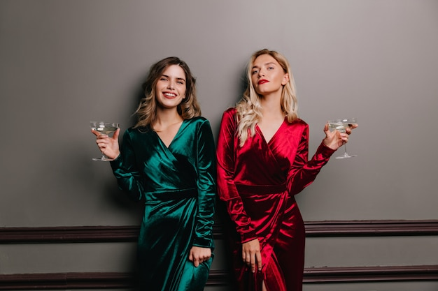 단정 한 갈색 머리 여자는 기쁨과 함께 와인을 마신다. 파티에서 포즈 매혹적인 재미있는 여자.