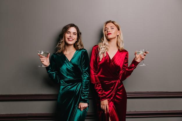 La donna castana ben vestita beve il vino con piacere. incantevoli ragazze divertenti in posa alla festa.