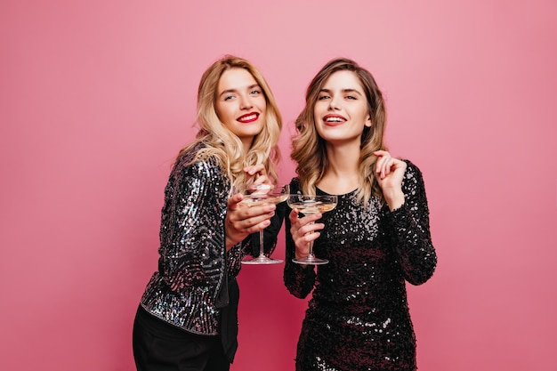 ピンクの壁にワインを飲む身なりのよいデボネアの女の子。パーティーでリラックスする魅力的な白人女性。
