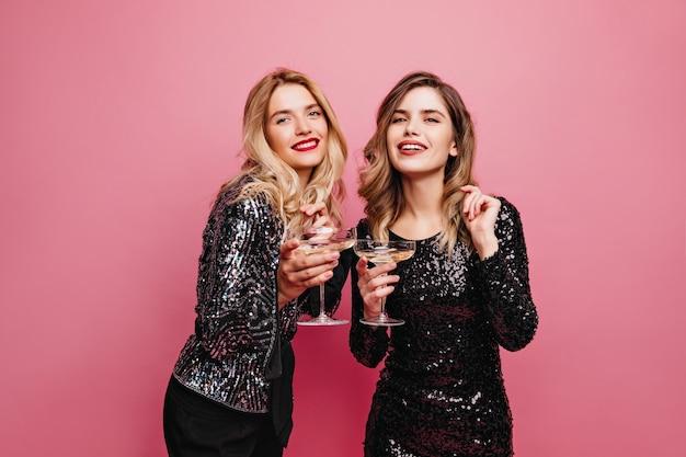 Ben vestita ragazza disinvolta che beve vino sul muro rosa. affascinanti signore caucasiche che si rilassano alla festa.