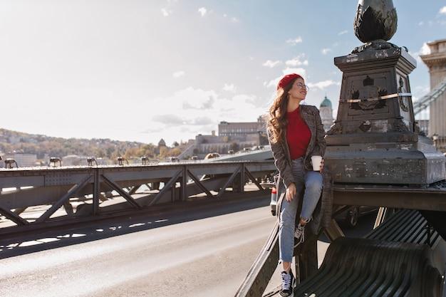 Turista femminile ben vestito che beve caffè sullo sfondo della città in una giornata ventosa