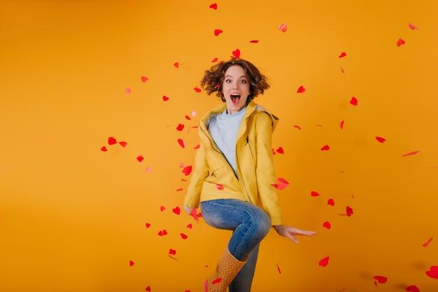 Хорошо одетая девушка танцует в окружении красных сердечек. внутреннее фото великолепной брюнетки женской модели, празднующей день святого валентина.