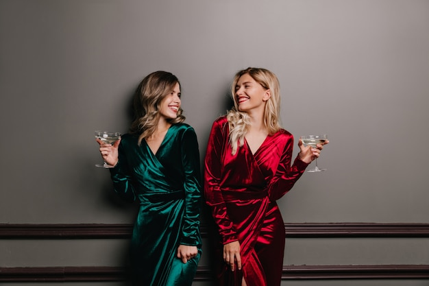 Well-dressed girls looking at each other while drinking wine. laughing friends enjoying conversation.