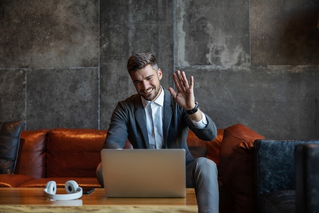 Well-dressed handsome businessman sitting on a couch and having a video call with colleagues. man is waving and saying goodbye. telecommunications, technologies, online zoom call meeting