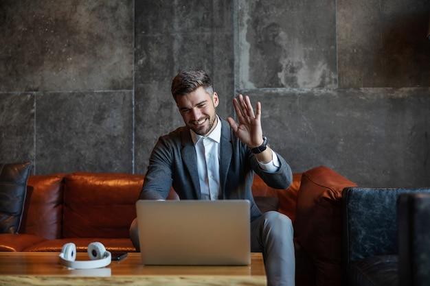Хорошо одетый красивый бизнесмен сидит на диване и разговаривает по видеосвязи с коллегами. мужчина машет рукой и прощается. телекоммуникации, технологии, онлайн-трансляция конференц-связи