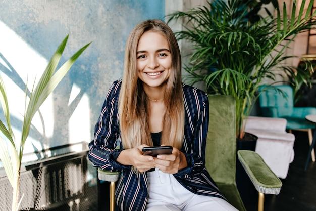 Хорошо одетая заинтересованная женщина сидит перед большим заводом. привлекательная смеющаяся девушка с телефоном отдыхает в кресле.