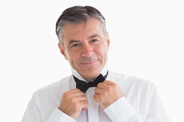 Well-dressed man adjusting his bow tie