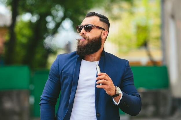 Хорошо одетый мужчина курит электронную сигарету