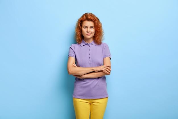 Donna seria ben vestita con le braccia conserte, porta le labbra, guarda dritto verso la telecamera, incerta