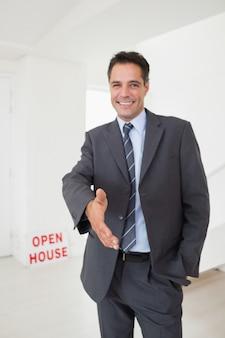 Well dressed smiling real estate agent offering handshake