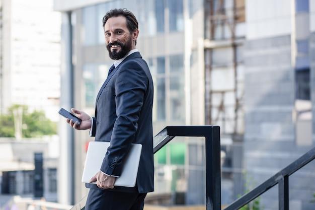 Хорошо одетый. подняв талию позитивного бородатого бизнесмена, держащего ноутбук во время использования смартфона