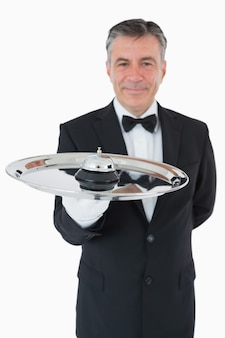 Well-dressed waiter holding a hotel bell in front of camera