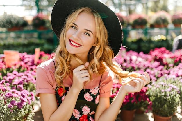 Donna ben vestita in posa davanti a fiori colorati. ritratto di donna allegra che gioca con i suoi capelli blinde.