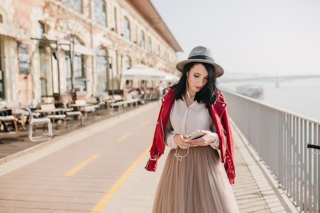 余暇に通りを歩いている帽子をかぶった身なりのよい若い女性