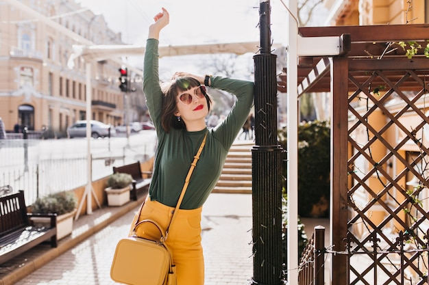 Giovane donna ben vestita in posa con le mani in alto sulla città. colpo all'aperto di beata ragazza bruna in occhiali da sole godendo il bel tempo.
