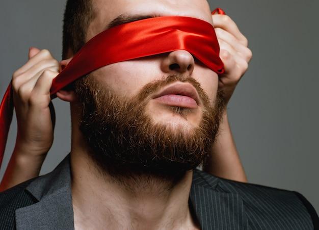 Ухоженный бородатый хипстер с завязанными глазами красной лентой