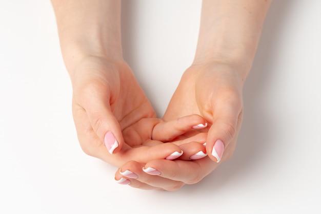 Ухоженные женские руки с маникюром на белом фоне