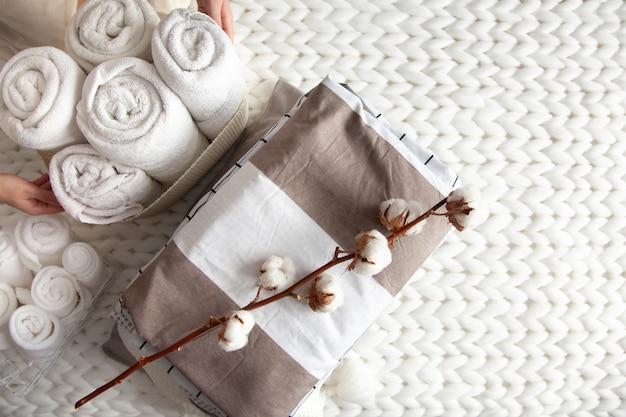 手入れの行き届いた女性の手が綿の枝を持ち、きちんと折りたたまれたリネンのスタックをメッシュバスケットに巻いたタオルの近くに置き、分厚いメリノ毛糸の格子縞を編みました。天然繊維。上面図。