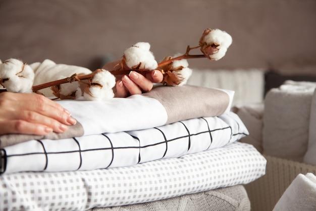 きちんと折りたたまれたベッドシーツ、毛布、タオルの山で綿の枝を保持している手入れの行き届いた女性の手。天然繊維の生産。製造。有機製品。