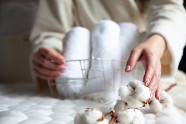 Руки ухоженной женщины держат корзину для хранения из металлической сетки с грудой свернутых белых полотенец на толстой шерстяной пряжи. хранение банных полотенец в порядке. текстильное производство. гостиничная индустрия