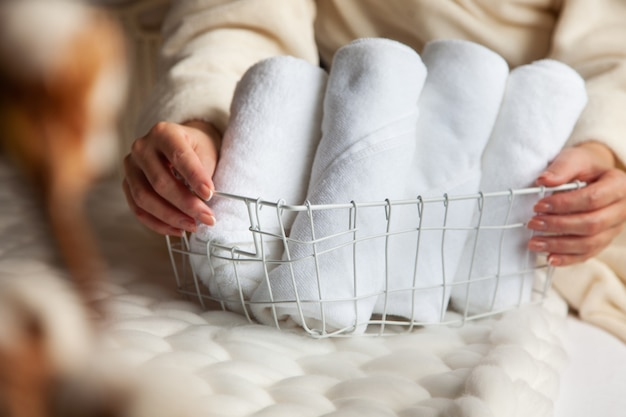 Well groomed woman's hands is holding metal mesh storage basket with pile of rolled up white towels on the thick woollen yarn. keeping bath towels organized. textile manufacturing. hotel industry